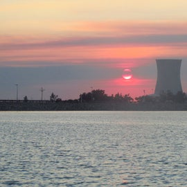 cooling tower near lake with sunset