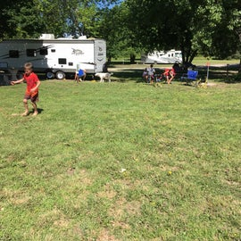 Clean camper area with grass to play on.