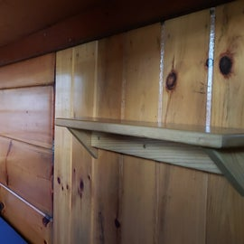 A bottom bunk with a reading light, shelf, and hooks, the ladder to upper bunks