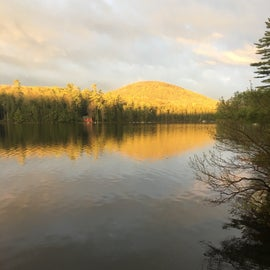 Morning sunrise looking over at a cabin across the pond from site #9