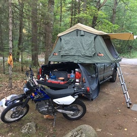 Great spot for tent / hammock setup! Shows here is the foot of the spot, and just behind where I'm standing is a nice little hill. The picnic table and firepit are located on top of this hill. The other side of the hill is a trail going down to the river. Third spot on the right when you first pass the Welcome sign in the park.