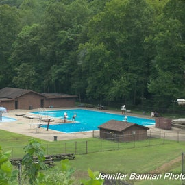 Outdoor pool complex with high dive, giant slide and kiddie pool.
