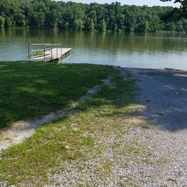 Boat dock next to ramp. Campsites are dispersed throughout the wooded areas, and along the shore.