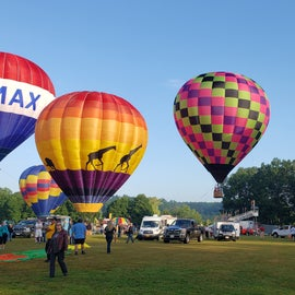 Suncook Valley Rotary Club Balloon Festival is nearby in early August. This morning it was too windy for takeoff, so they were staying tethered to the groun.