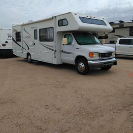 Our small rig in a regular RV space with full hookups. The road is paved, and the parking for the rigs are on a well-draining mix of dirt and sand.