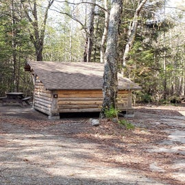 Lean-to along the stream, the back to the road for privacy