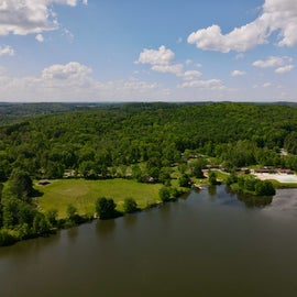 Overview of the main area of the campgrounds, the large lawn and playground area, and the pool.
