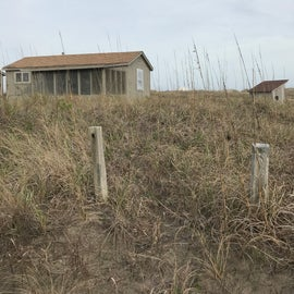 Cabin 22 at a distance. Beach directly behind cabin over dunes.