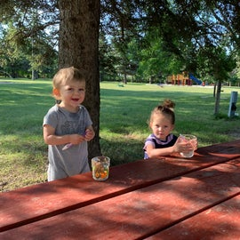 Breakfast outside at the picnic table (playground in background). Lots of green grass in between spots.