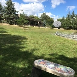 artsy sculptural benches by campsite, with outdoor amphitheater to the right