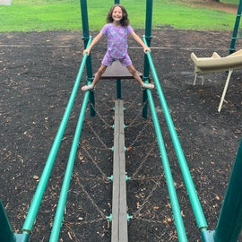 Enjoying the playground , in the back ground you can see one of the bathhouses within the campground