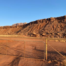 """Gate from the inside, facing highway 89. """"Scenic Byway"""" sign is circled."""