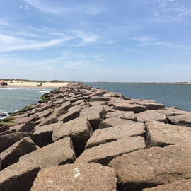 View looking back west from the end of the North Jetty. South Padre Island is on the left, the Port Mansfield Channel is on the right, and the sliver of land on the other side of the channel (far right of photo) is the southern tip of North Padre Island / Padre Island National Seashore (no access except across Channel by boat).