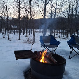Fire pit and wooded area at campsite 202