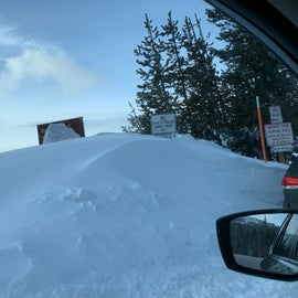 Signs posted by entrance; the brown sign is the Dutchman Sno-park sign covered with snow.