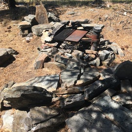 Someone made chairs for the fire out of flat stones from the lake.