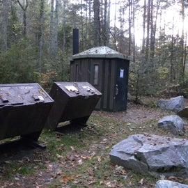 Dumpsters are close to the pit toilet.
