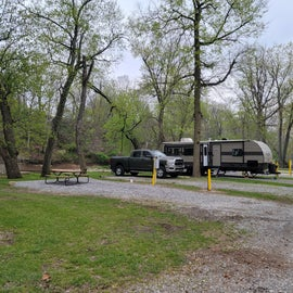 View of site 43 (empty) and 41 (with truck and brown RV). 41 is a double site so u can park your vehicle there.