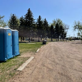 porti potty's available and flush toilets in the white building
