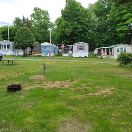 Our site (in the forefront) was grassy with picnic table and fire pit but not very level for our coach.