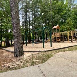 Playground by lake. Bathhouse behind