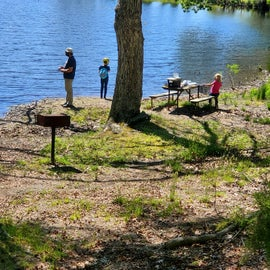 dad and 2 daughters fishing on small pond