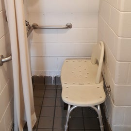 ADA shower has a nice bench and rails