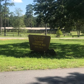 Entrance sign with horse corrals in background.