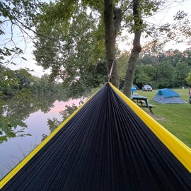 Picture of hammock with river view and campsites with water view in the background.