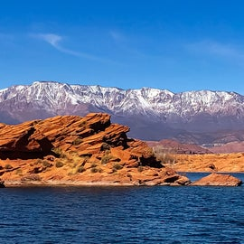 beautiful red rock with snow capped mountains in the background